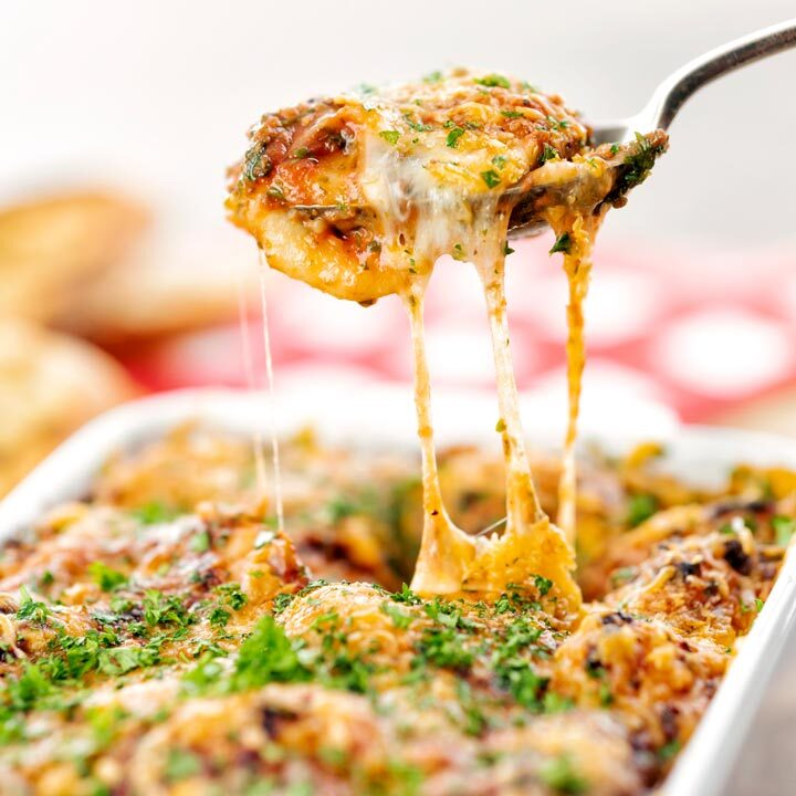 Square close up image of gnocchi alla Sorrentina served in a gratin dish being served with a spoon showing gooey mozzarella cheese strings