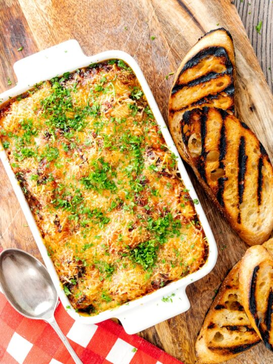 Portrait overhead image of gnocchi alla Sorrentina served in a gratin dish with griddled bread