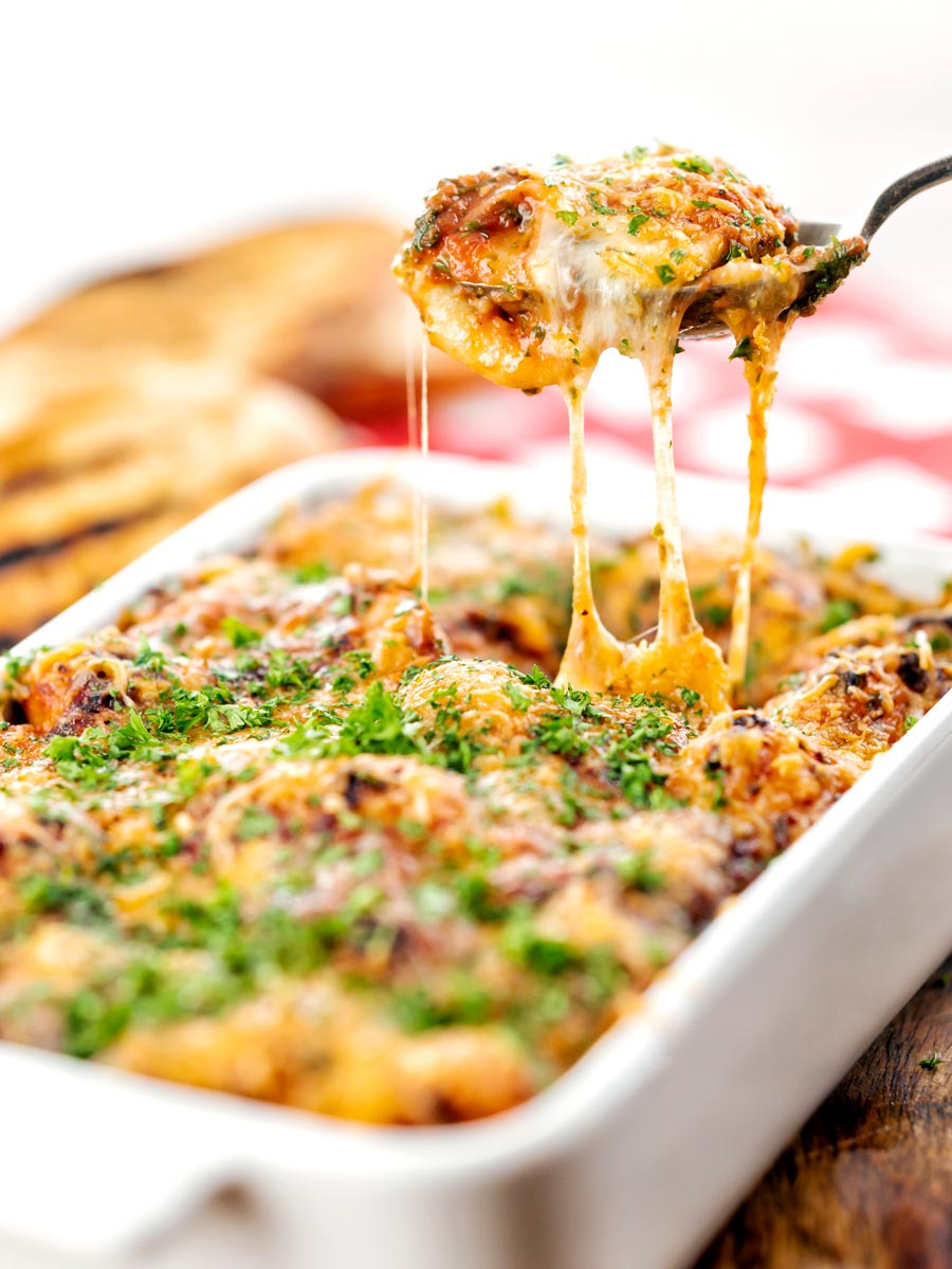 Portrait image of gnocchi alla Sorrentina served in a gratin dish being served with a spoon showing gooey mozzarella cheese strings