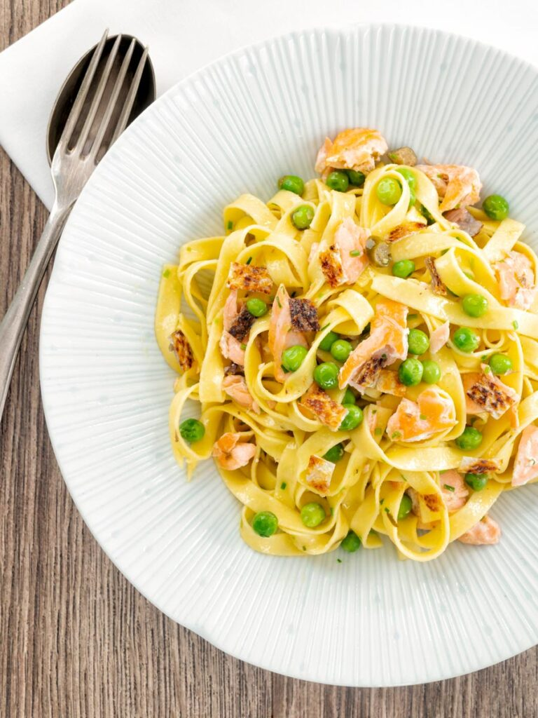 Portrait overhead image of salmon and pea pasta with tagliatelle pasta and crispy salmon skin and snipped chives