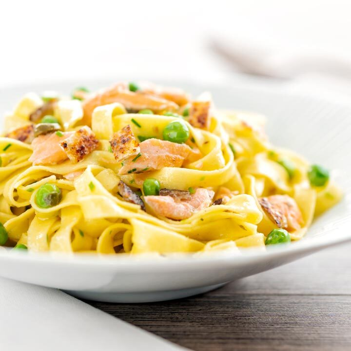 Square image of salmon and pea pasta with tagliatelle pasta and crispy salmon skin and snipped chives