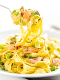 Portrait image of salmon and pea pasta with tagliatelle pasta and crispy salmon skin and snipped chives being picked up with a fork