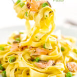 Portrait image of salmon and pea pasta with tagliatelle pasta and crispy salmon skin and snipped chives being picked up with a fork featuring a title overlay