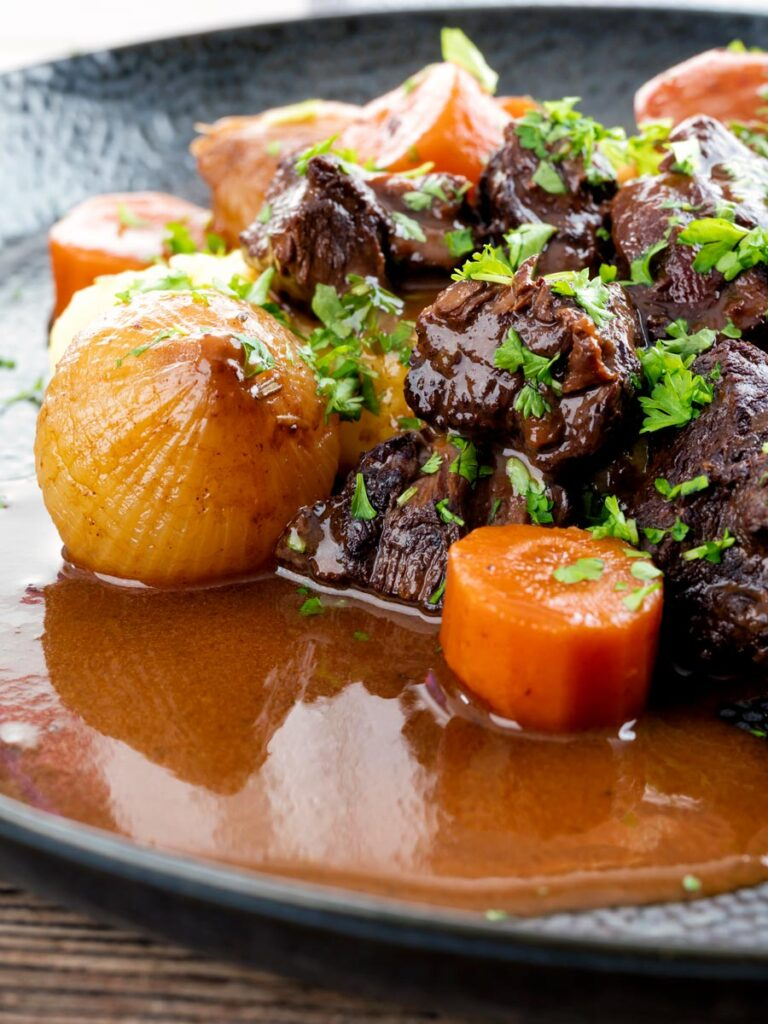 Portrait close up image of a slow cooker beef daube featuring carrots and whole small onions garnished with parsley