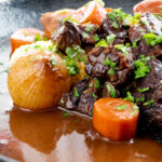 Portrait close up image of a slow cooker beef daube featuring carrots and whole small onions garnished with parsley featuring a title overlay