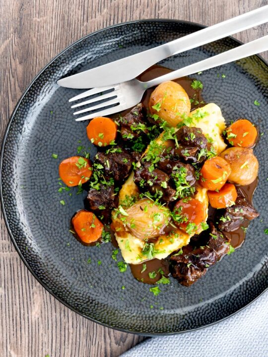 Portrait overhead image of a slow cooker beef daube featuring carrots and whole small onions, served with mashed potato and garnished with parsley