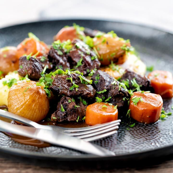 Square image of a slow cooker beef daube featuring carrots and whole small onions served with mashed potato and garnished with parsley