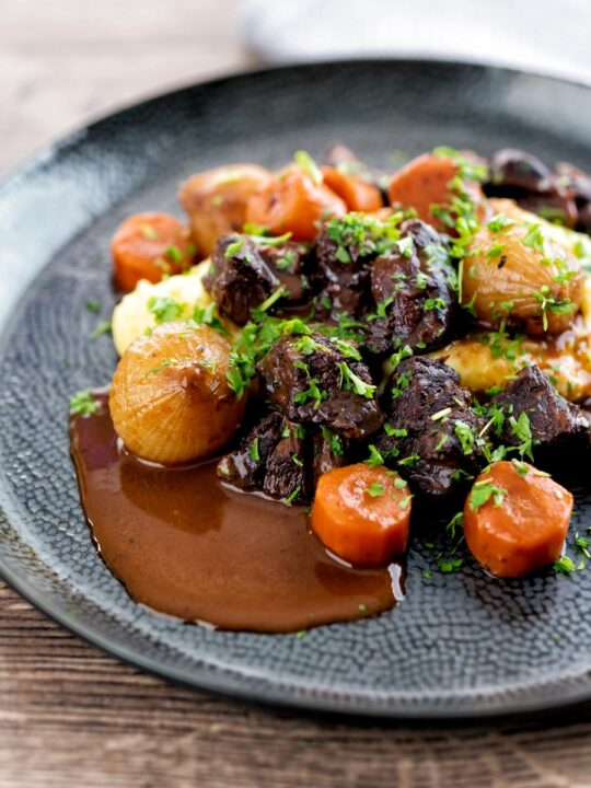 Portrait image of a slow cooker beef daube featuring carrots and whole small onions served with mashed potato and garnished with parsley