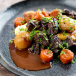 Portrait image of a slow cooker beef daube featuring carrots and whole small onions served with mashed potato and garnished with parsley featuring a title overlay