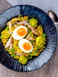 Portrait overhead image of an Indian inspired smoked mackerel kedgeree with boiled eggs and leeks