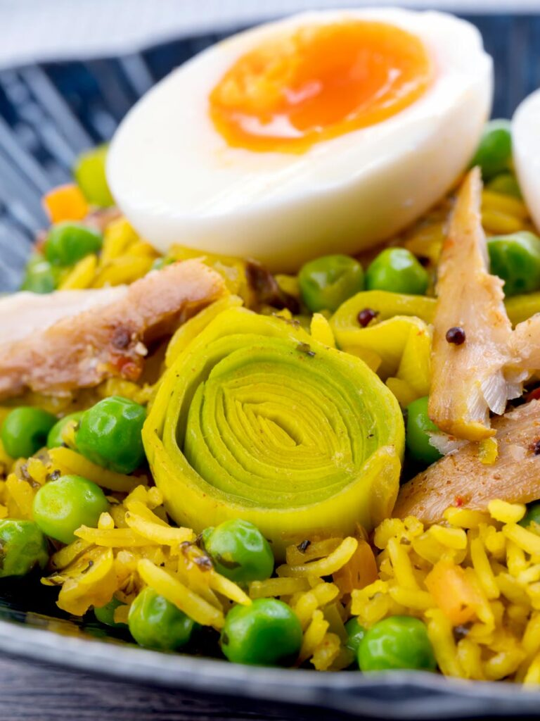 Portrait close up image of an Indian inspired smoked mackerel kedgeree with boiled eggs and leeks