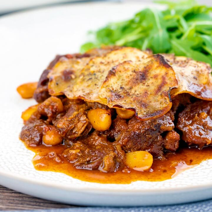 Square image of a sliced potato topped spicy beef hotpot with dried almonds and apricots