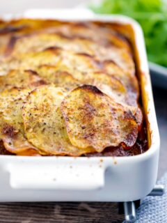 Portrait image if a sliced potato topped spicy beef hotpot served in a gratin bowl