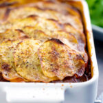 Portrait image if a sliced potato topped spicy beef hotpot served in a gratin bowl featuring a title overlay