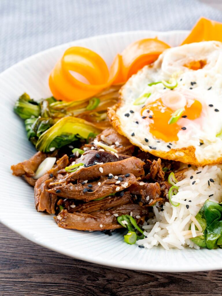 Portrait image of a teriyaki duck donburi rice bowl with a fried egg
