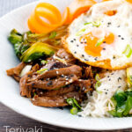 Portrait image of a teriyaki duck donburi rice bowl with a fried egg featuring a title overlay