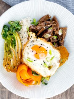 Portrait overhead image of a teriyaki duck donburi rice bowl with a fried egg & bok choi