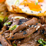 Portrait close up image of a teriyaki duck donburi rice bowl with a fried egg featuring a title overlay