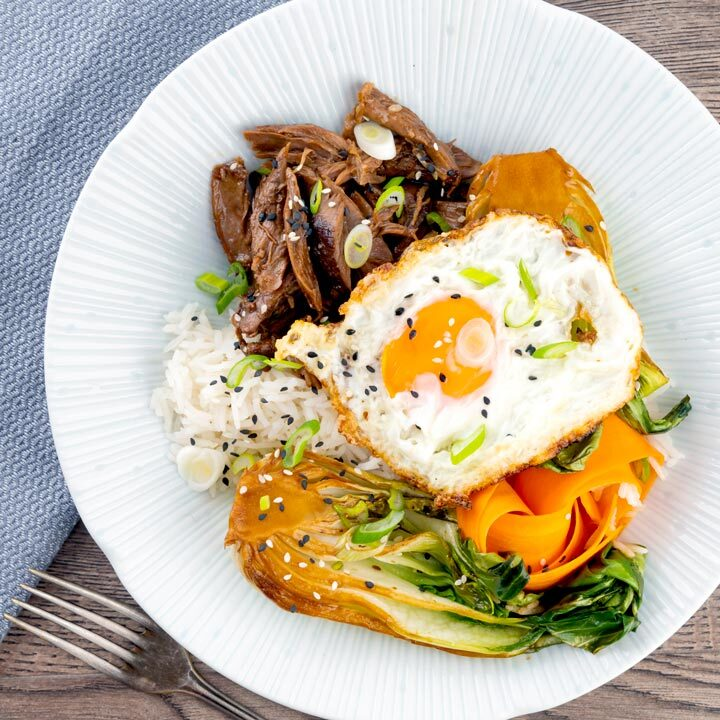Square overhead image of a teriyaki duck donburi rice bowl with a fried egg & bok choi