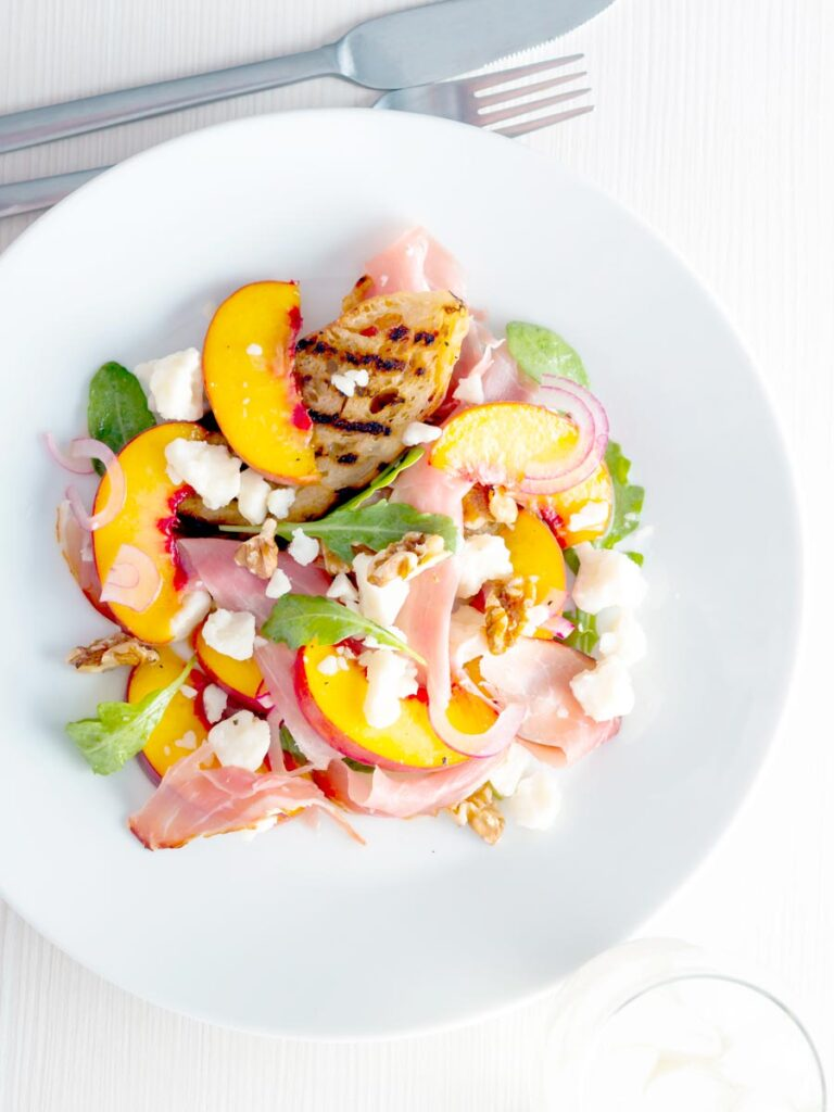 Overhead image of a pickled peach and goat cheese salad with Parma ham and chopped walnuts.