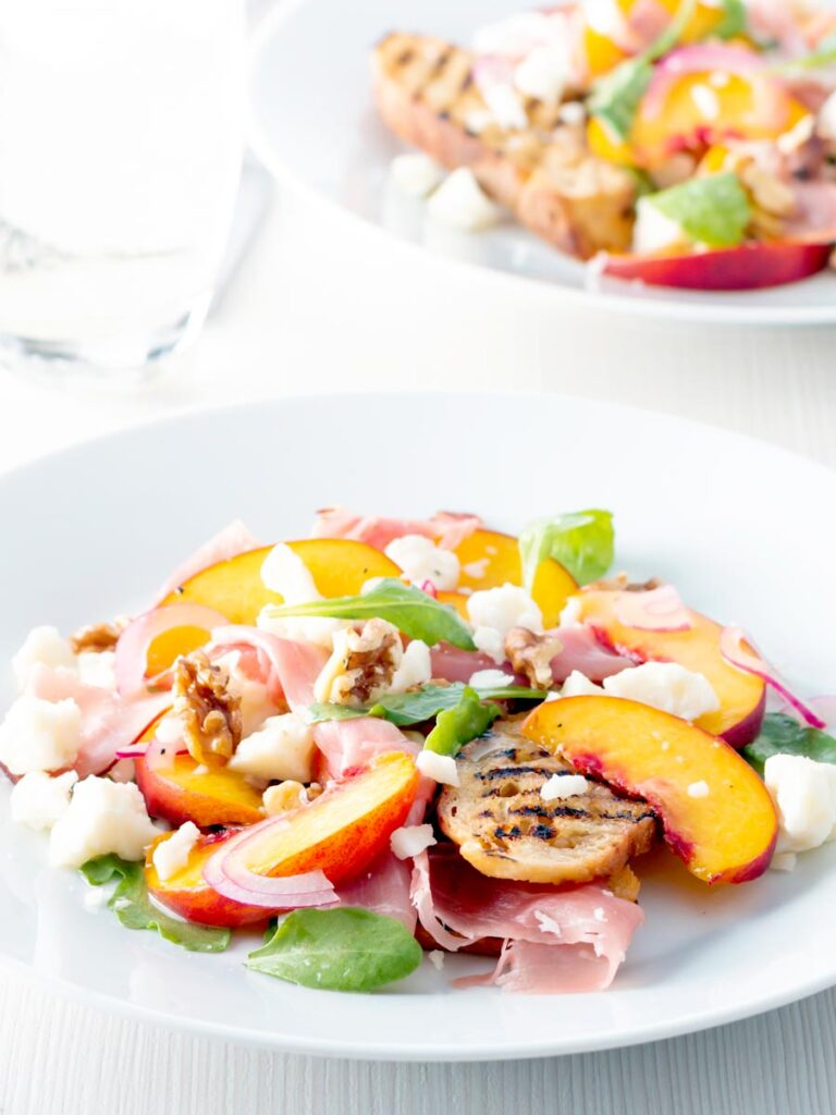 Two plates of pickled peach and goat cheese salad with Parma ham and chopped walnuts.