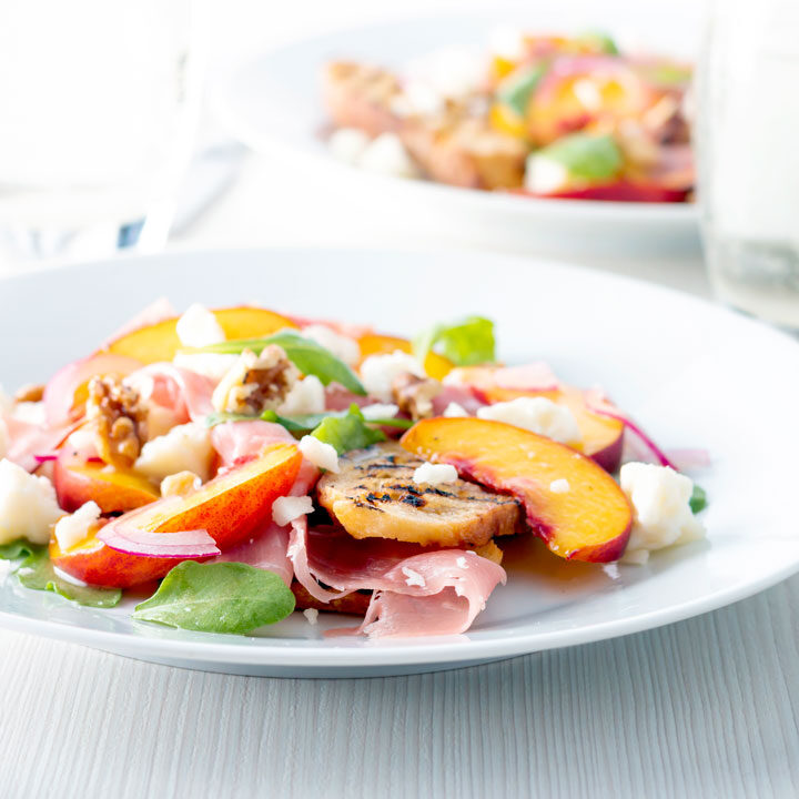 Square image of a pickled peach and goat cheese salad with Parma ham and chopped walnuts.