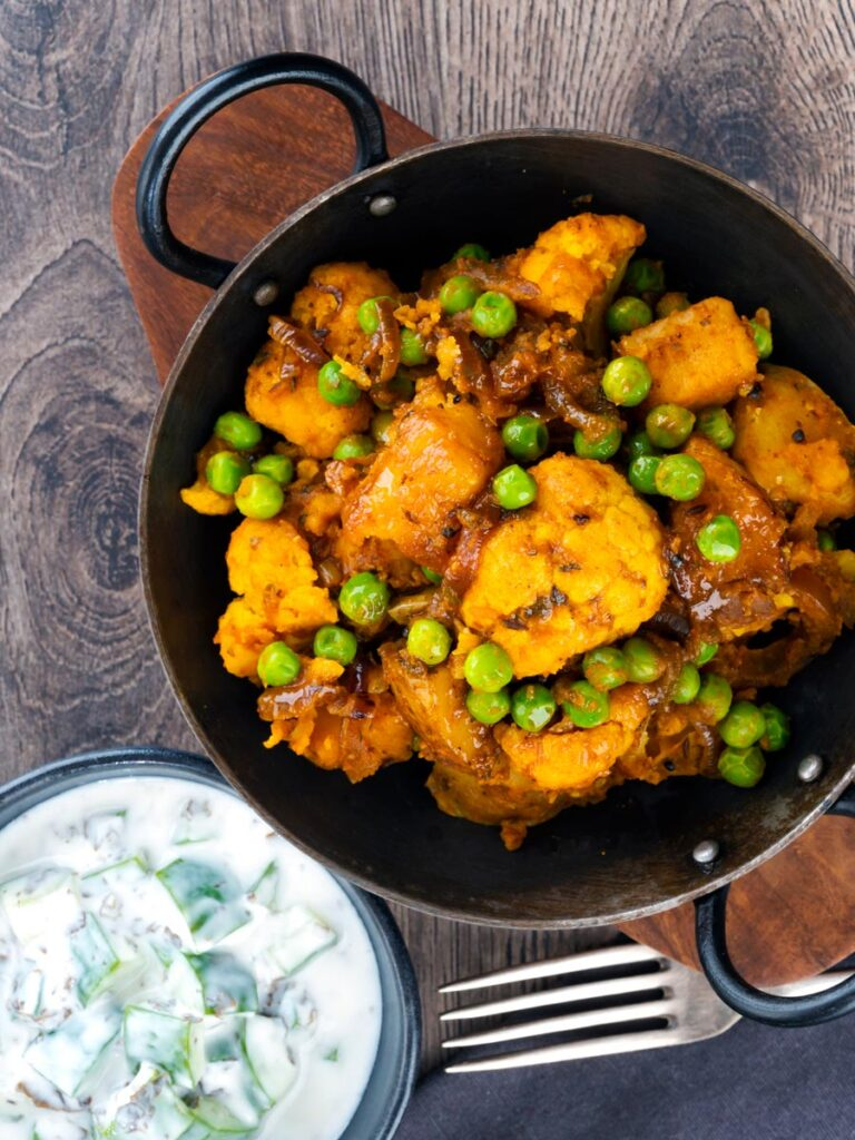 Overhead picture of an aloo gobi matar curry served with a cucumber and mint raita