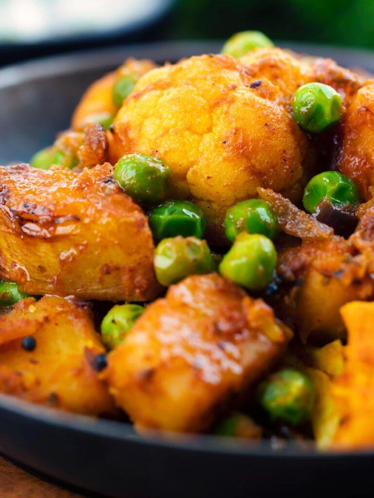 Close up Aloo gobi matar curry served served in an iron karai