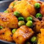 Close up Aloo gobi matar curry served served in an iron karai featuring a text overlay
