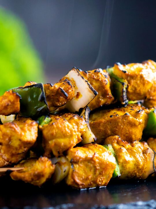 Close up steaming hot Chicken tikka kebabs with onion and green pepper