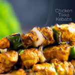 Close up steaming hot Chicken tikka kebabs with onion and green pepper featuring a title overlay