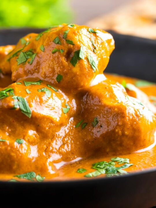 Close up creamy rich chicken tikka masala curry in an iron karai