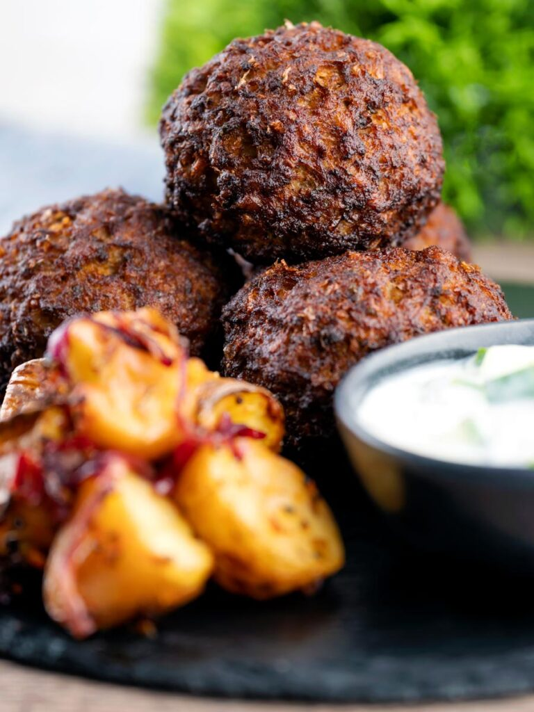 Nargis kebab or Indian Scotch eggs served with Bombay potatoes and cucumber raita