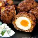 Nargis kebab or Indian Scotch eggs with one cut open to show jammy yolk served with cucumber raita featuring a title overlay