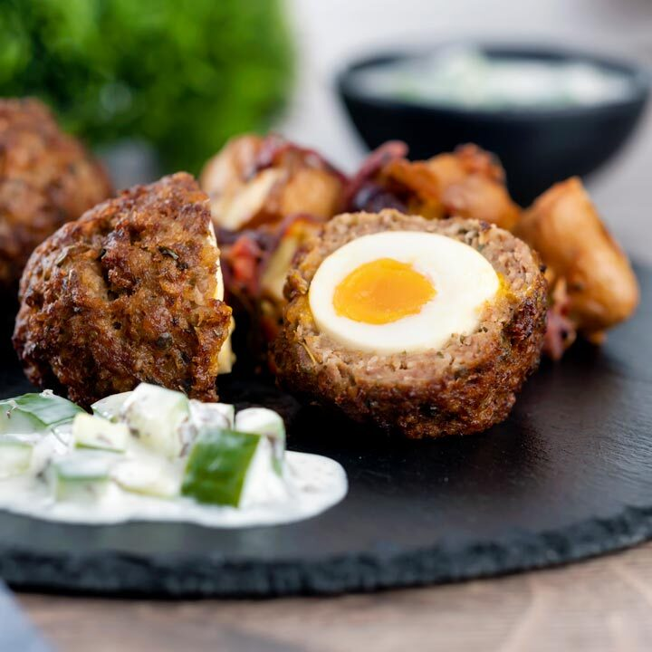 Nargis kebab or Indian Scotch eggs with one cut open to show jammy yolk served with cucumber raita