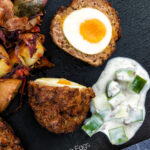 Overhead Nargis kebab or Indian Scotch eggs with one cut open to show jammy yolk served with cucumber raita featuring a title overlay