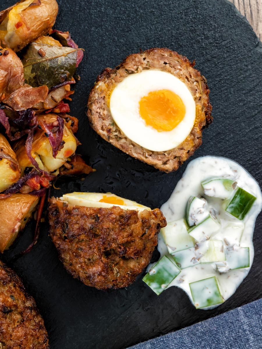Overhead Nargis kebab or Indian Scotch eggs with one cut open to show jammy yolk served with cucumber raita