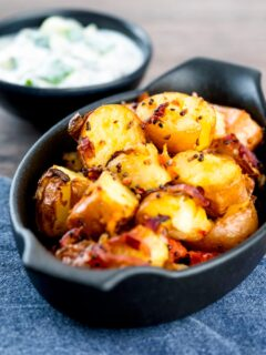 Roast Bombay potatoes or Bombay aloo in a black earthenware bowl served with raita