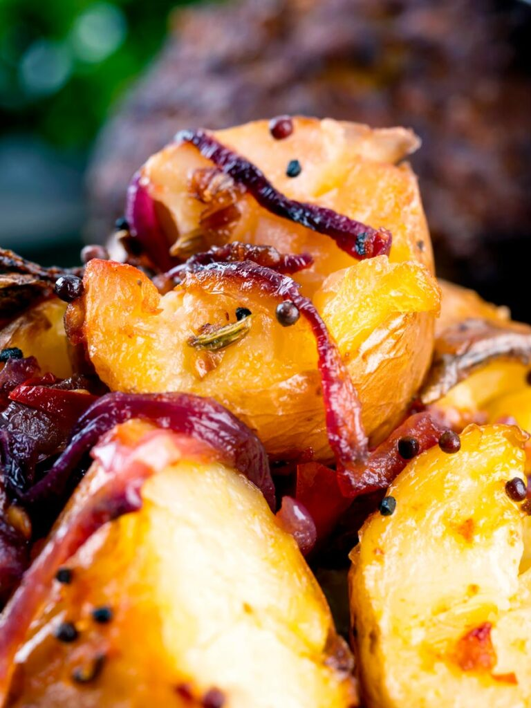 Close up Roast Bombay potatoes or Bombay aloo with red onion and mustard seeds