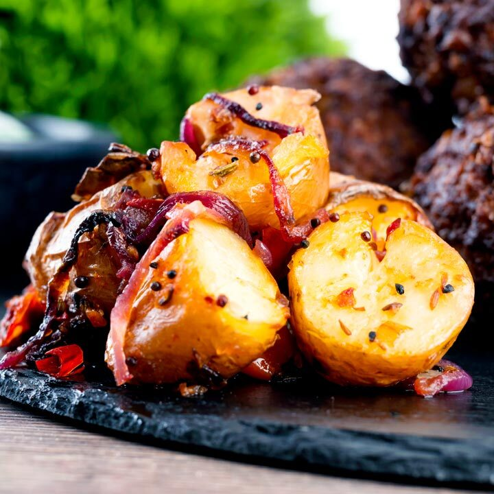 Roast Bombay potatoes or Bombay aloo served on a slate as a side dish