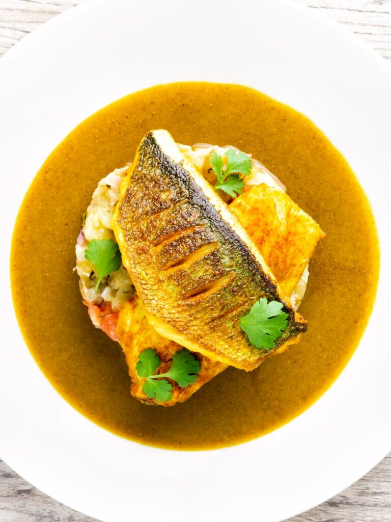 Overhead sea bass fillet curry served with fenugreek potatoes