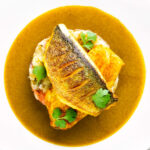 Overhead sea bass fillet curry served with fenugreek potatoes featuring a title overlay