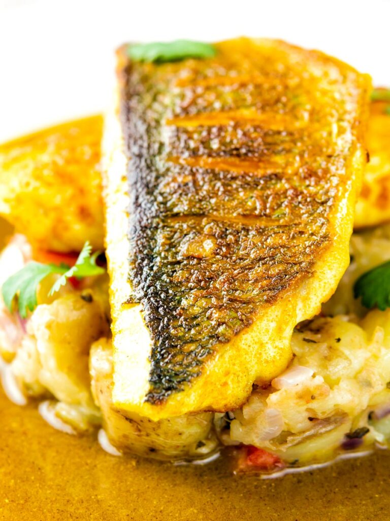 Close up Sea bass curry featuring a tamarind curry sauce & Fenugreek potatoes