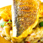 Close up Sea bass curry with a tamarind curry sauce & Fenugreek potatoes featuring a title overlay