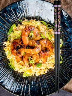 Overhead image of Teriyaki prawns stir fry served on egg fried rice with spring onions