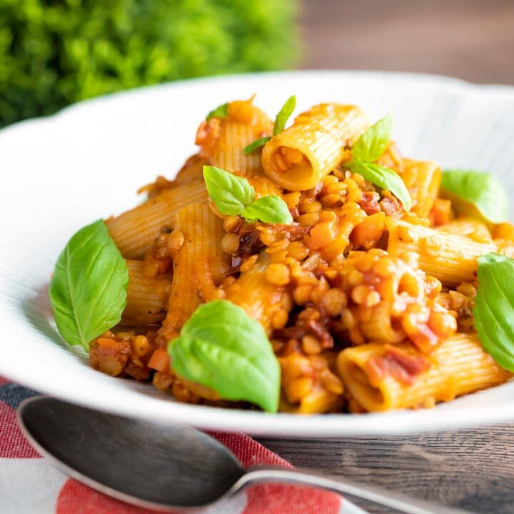 Close up vegan red lentil ragu or bolognese served with rigatoni pasta and fresh basil leaves.