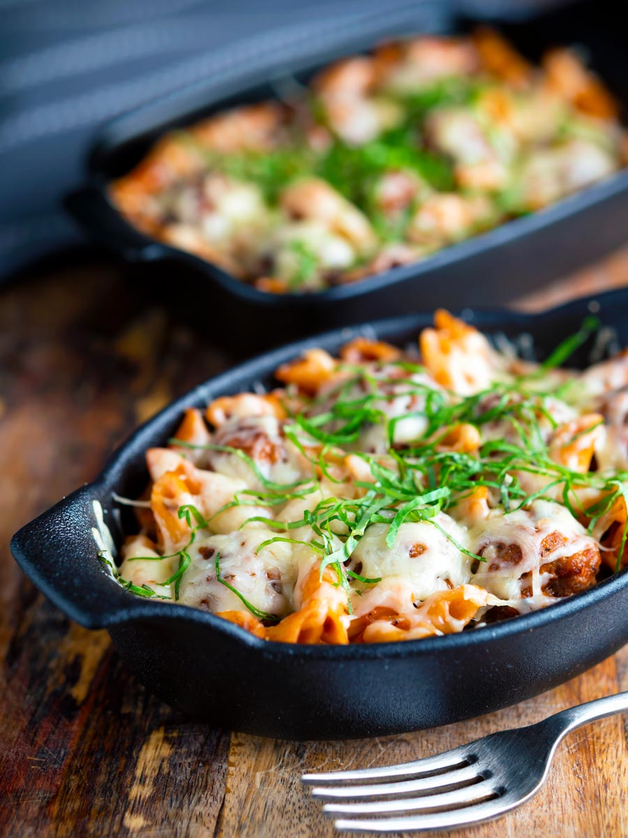 Cheesy meatball pasta bake served in individual stoneware bowls.