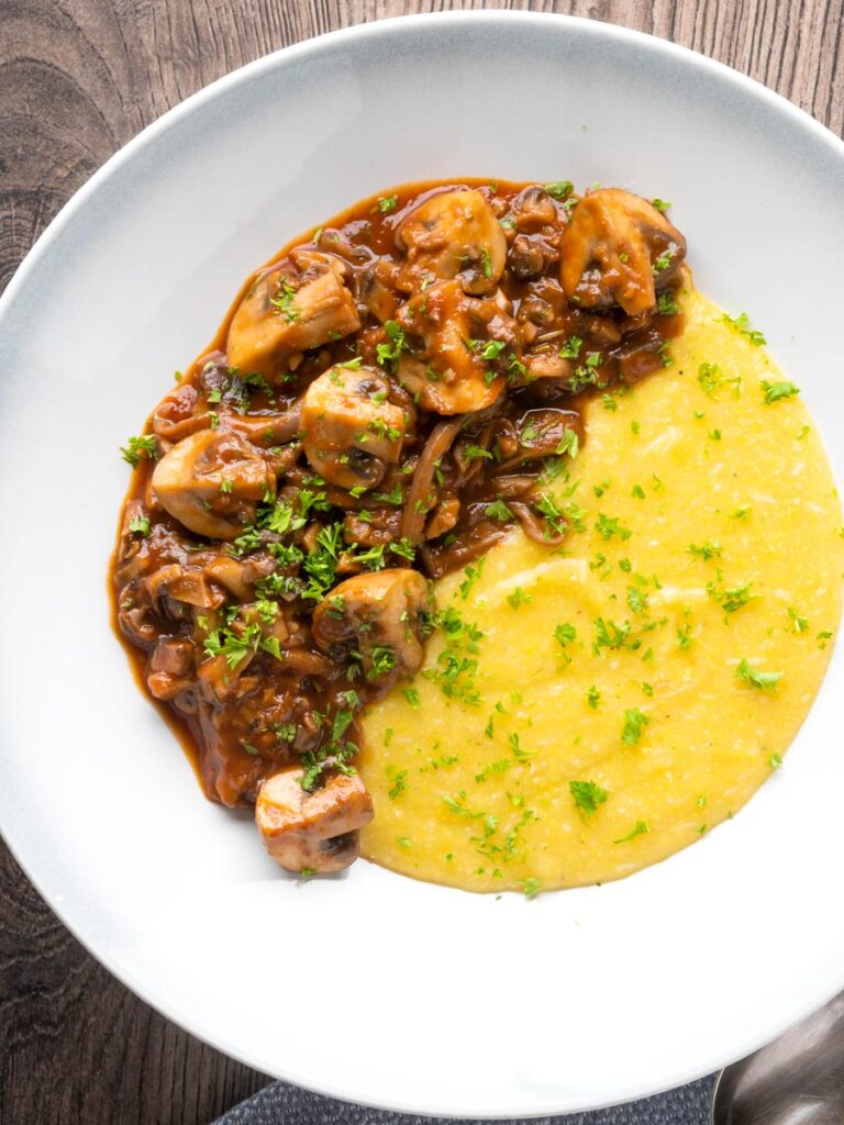 Overhead vegan mushroom ragu served with polenta and a parsley garnish