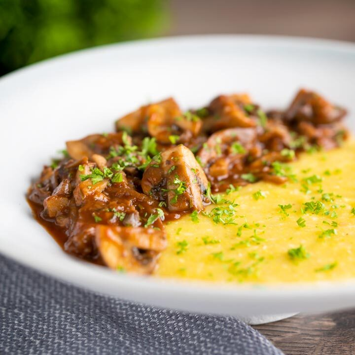 Super chunky vegan mushroom ragu served with polenta and a parsley garnish.