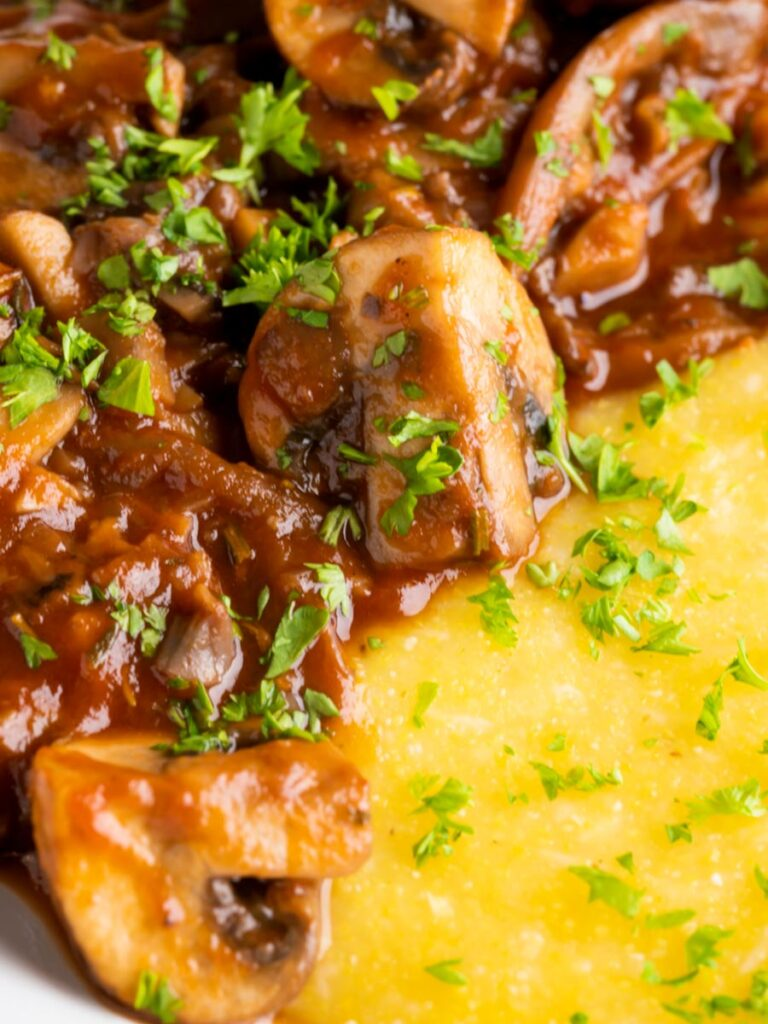 Close up vegan mushroom ragu served with polenta and a parsley garnish